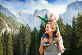 Happy mother and her child looking forward and pointing to sky. Family on trekking day in the mountains. Mangart Julian Alps National Park Slovenia Europe. Travel Explore Family Future Concept poster