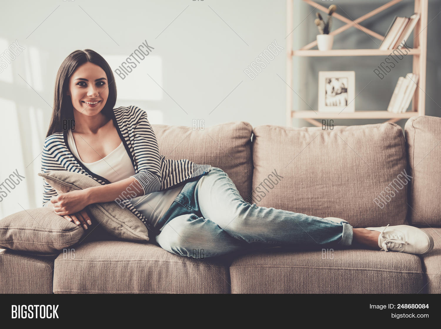Young Smiling Woman In Jeans Lying On Sofa At Home Hy Relaxing