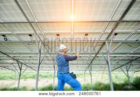 Young Electrician Connecting Electrical Cables Inside The Lit By Sun Solar Modules. Installing And W