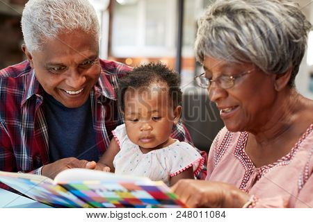 Grandparents Reading Book With Baby Granddaughter At Home poster