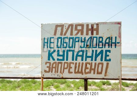 Warning Sign On The Shore. Text In Russian: The Beach Is Not Equipped. Swimming Is Forbidden