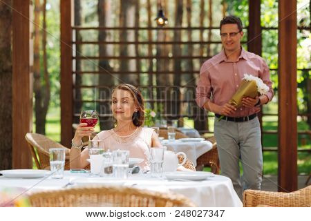 Waiting For Husband. Blonde-haired Beaming Woman Drinking Glass Of Wine Waiting For Her Handsome Hus