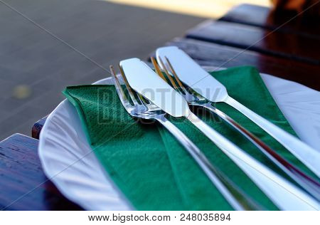 Cutlery In A Restaurant With Green Napkin, Fish Knife, Fork And Plate
