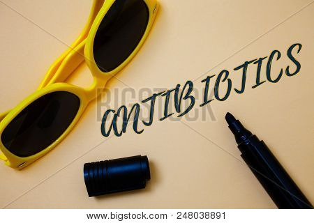 Writing note showing  Antibiotics. Business photo showcasing Antibacterial Drug Disinfectant Aseptic Sterilizing Sanitary Ideas messages beige background black marker markers yellow sunglasses poster