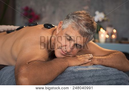 Mature man relaxing on bed during hot stone massage. Portrait of senior man with closed eyes resting during lastone therapy. Handsome man with black lava stone on back at spa with candles.