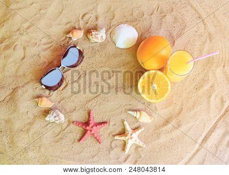 Glass Of Orange Juice, Oranges, Sunglasses, Starfishes And Seashells On Sand Beach