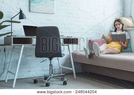 Teen Girl With Cup Of Coffee Reading Book On Fosa In Room With Table And Laptop