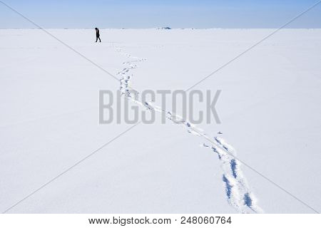 Footsteps Of Lonely Person Walking Along The Endless Snowfield