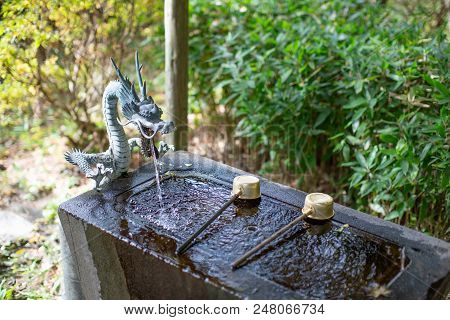 The Water Purification Basin temizuya or chozuya in Japanese temple. The cleansing hands and mouth ritual in Japanese temple or shrine. The dragon fountain. poster