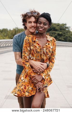 Curly Caucasian Man Embracing Wonderful Stylish Black Woman From Back Both Looking Smilingly At Came