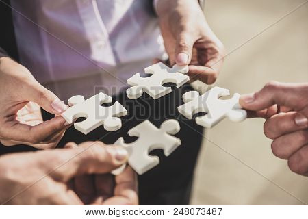 Close Up. Hands Of Businesswoman And Businessman Solves Puzzle. Agreement Concept. Successful Busine