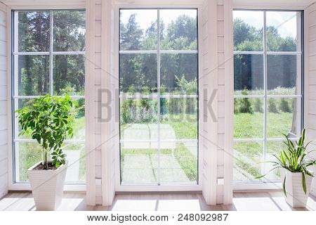 Bright Interior Of The Room In A Wooden House With A Large Window Overlooking The Summer Courtyard.