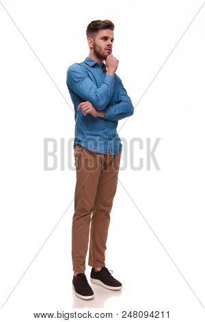 pensive casual man with beard looks to side while standing on white background, full body picture
