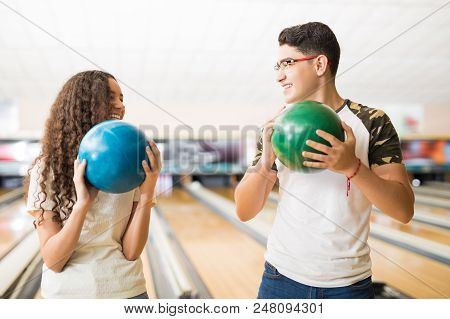 Smiling Teen Couple Holding Balls While Looking At Each Other In Bowling Club