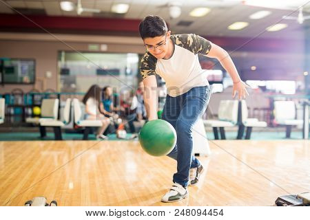 Full Length Of Confident Teenage Boy Practicing His Swing At A Bowling Alley