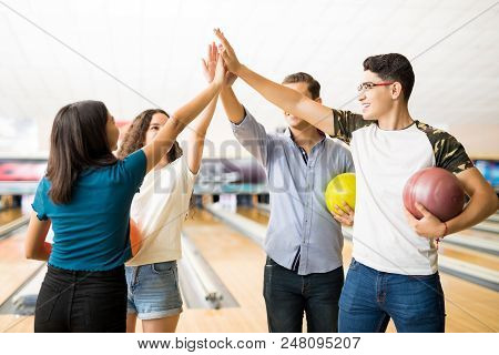 Male And Female Teenage Friends Giving High-five While Holding Bowling Balls At Alley In Club