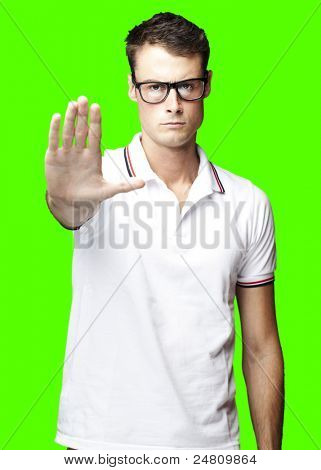portrait of young man doing stop symbol over a removable chroma key background