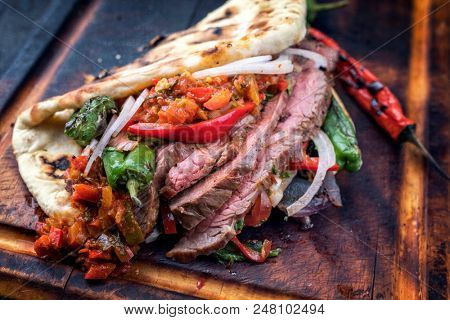 Barbecue dry aged wagyu flank steak chili relish and vegetable in a flatbread on a burnt board