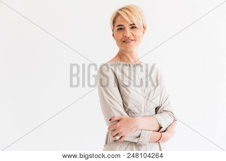 Portrait of cheerful mature blond woman 40s looking at camera with kind smile and arms folded isolated over white background in studio