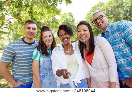 people, friendship and international concept - happy smiling young woman and group of happy friends taking picture by selfie stick outdoors