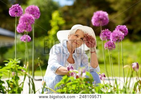 gardening and people concept - tired senior woman or gardener with flowers working at summer garden