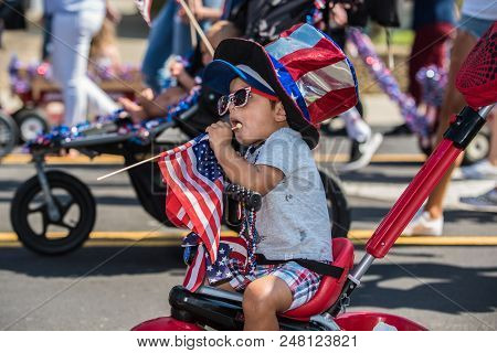 Young Child Wearing Patroitic Red, White, And Blue Colors Of The Flag While Participating In Indepen
