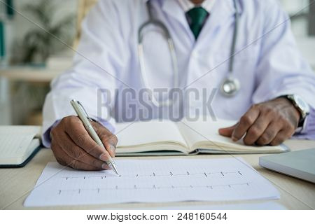 Close-up Image Of Cardiologist Checking Cardiogram Of Patient