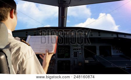 Pilot In The Cockpit Of A Small Commercial Aircraft Above A Rural Landscape, Cloudy Sky Background.