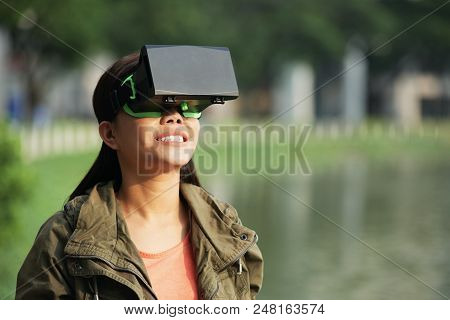 Portrait Of Smiling Young Woman In Vr Glasses Standing Outdoors
