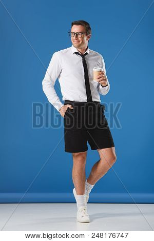Handsome Smiling Man In Eyeglasses Holding Coffee To Go While Standing With Hand In Pocket Of Shorts