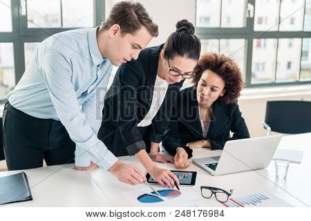 Young team of three business experts interpreting pie chart printed on paper in the office poster