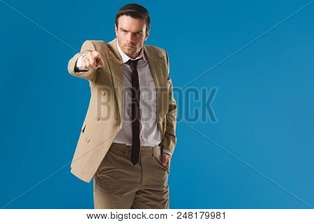 Serious Man Standing With Hand In Pocket And Pointing At Camera Isolated On Blue