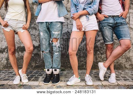 Another Picture Of People's Legs. These Human Beings Are Posing On Camera. Girls Have Bended Legs In