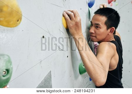Young Asian Man Working Out In Bouldering Center And Climbing Wall With Concentration Grabbing Color