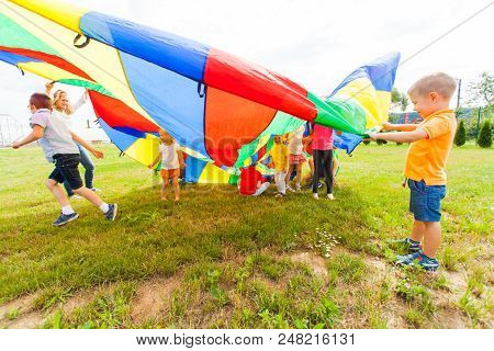 Small Laughing Boy Is Covering A Group Of Kids With Colorful Parachute, Summer Camp Outdoor Games