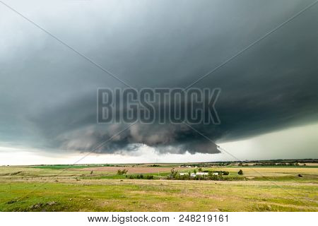 Large, powerful tornadic supercell storm moving over a small town in Oklahoma sets the stage for the formation of tornados across Tornado Alley.