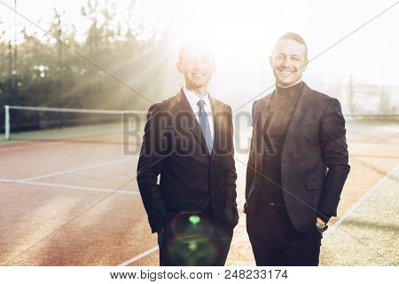 Two Handsome Young Businessmen In Classic Clothes Are Looking At Camera And Smiling, Standing In Sun