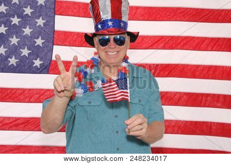A happy Smiling American Man with an American Flag Background. Photo Booth portrait of a Proud American. Man in a 4th of July Photo Booth.