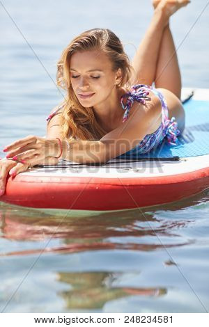 SUP Stand up paddle board woman paddle boarding on lake standing happy on paddleboard on blue water.