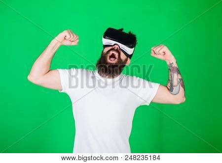 Man With Beard In Vr Glasses, Green Background. Hipster On Shouting Face Raising Hands Powerfully Wh