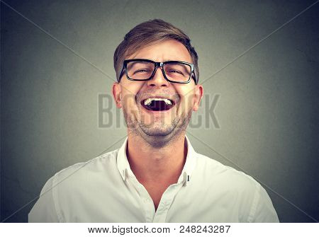 Causal young man in white shirt and black glasses laughing from humorous joke. poster