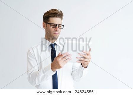 Portrait Of Serious Young Executive Using Digital Tablet. Caucasian Student In Glasses Using Touchpa