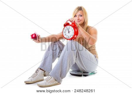 Diet, fitness, slimming, loosing weight concept. Curvy woman holding apple, measuring tape and big old fashioned clock sitting on weighing machine poster