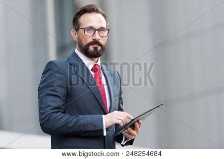 Portrait Of Businessman With Tablet In Hand On Background Of Office Building. Businessman Using His