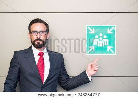 Handsome Professional Leader Pointing To Meeting Point Sign. Man In Suit And Red Tie Warning About P