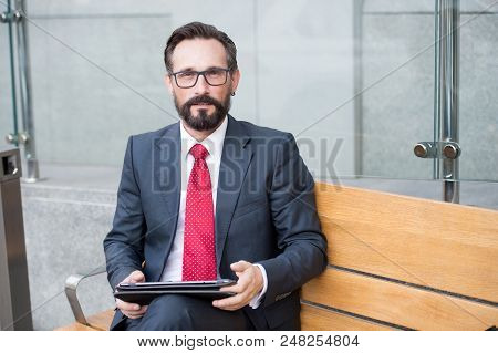 Relaxed Businessman In Glasses Using His Pc Tablet While Sitting On Bench. Senior Businessman Using