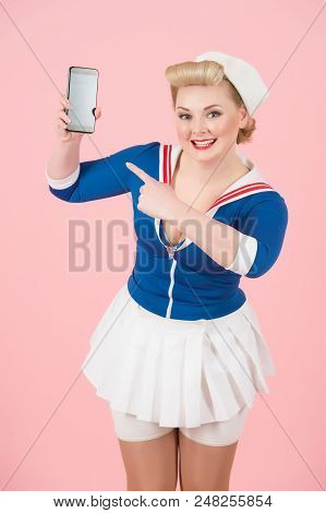 Pretty Pin-up Styled Girl Pointing To Smart-phone With Message. Pin-up Style With Modern Communicati
