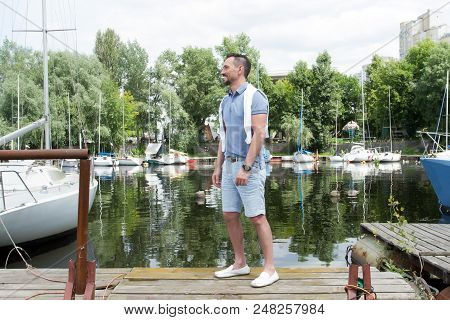 Young Man Goes To His Yacht In The River Bay. Successful Guy In Sea Bay With Yacht. Summertime For S