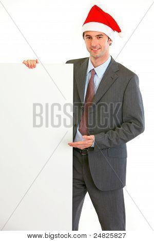 Smiling Modern Businessman In Santa Hat Showing Blank Billboard