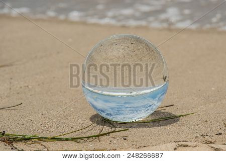 Glass Globe On Beach Shore Looks To Be Full Of Sky And Magnified Sand.